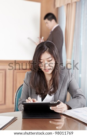 Chinese businesswoman busy working with her tablet while businessman on background busy preparing presentation - stock photo
