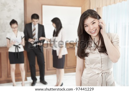Chinese businesswoman is on the phone in the office - stock photo