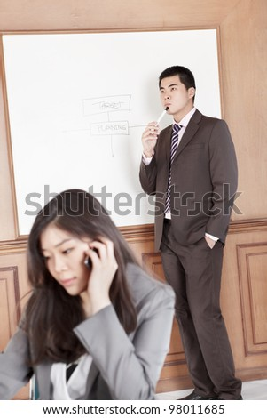 Chinese businesswoman on the phone while businessman preparing presentation on background - stock photo