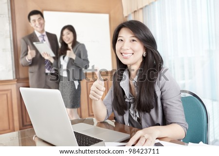 Chinese businesswoman showing her thumb up in the office - stock photo