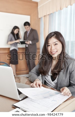 Chinese businesswoman smiling to the camera in the office - stock photo