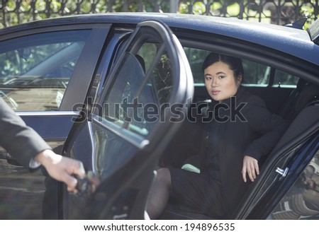 Chinese businesswoman stepping out of limousine. Business travel: chauffeur opening car door for business executive. - stock photo