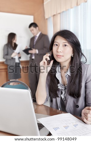 Chinese businesswoman talking on cell phone in the office - stock photo