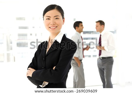Chinese businesswoman with partners in the background - stock photo