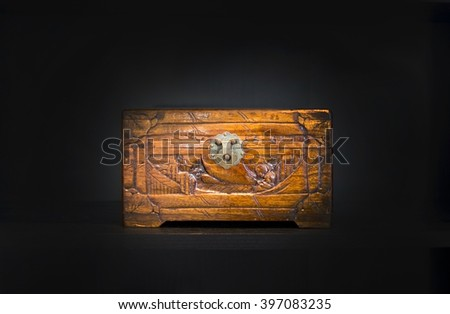 Chinese carved wooden box with metal lock on dark background.