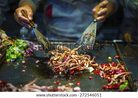 Chinese Chef making Iron Squid. Located in old town of Lijiang, Yunnan Province, China. - stock photo