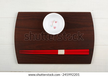 Chinese chopsticks on a wooden plate - stock photo