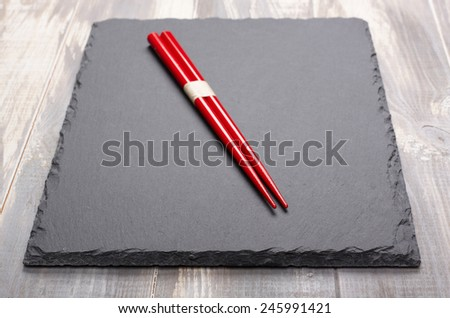 chinese chopsticks on slate plate - stock photo
