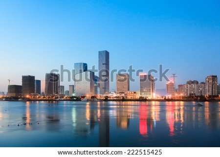 Chinese City CBD  at dusk,Fuzhou,China. The development of Fuzhou's new central business district by minjiang river.  - stock photo