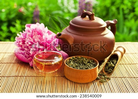 Chinese clay teapot with glass cup, green tea, scoop and peony flower - stock photo