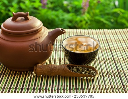 Chinese clay teapot with green tea  - stock photo