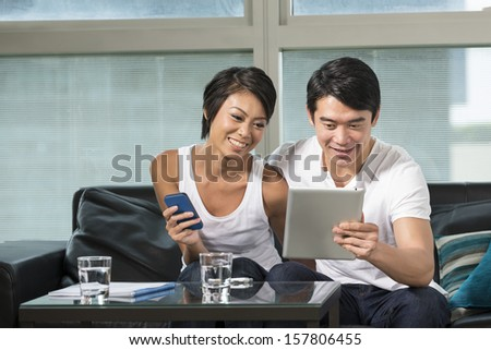 Chinese couple relaxing with a digital tablet in their living room - stock photo