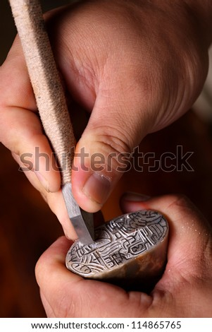 Chinese craftsman carving a stone seal