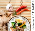 Chinese cuisine beef stir fry with vegetables on white rice, bamboo mat background with raw ingredients - stock photo