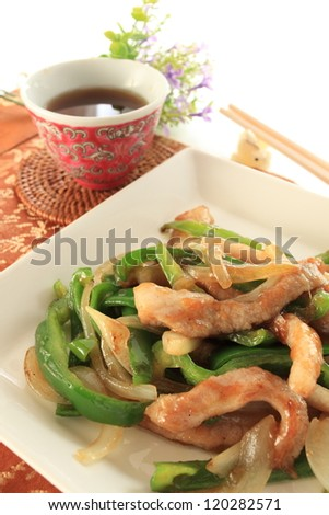 chinese cuisine, pork and pepper stir fried and black tea with chopstick - stock photo