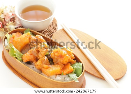 Chinese cuisine, sweet and sour spare  on rice in Japanese bento style - stock photo