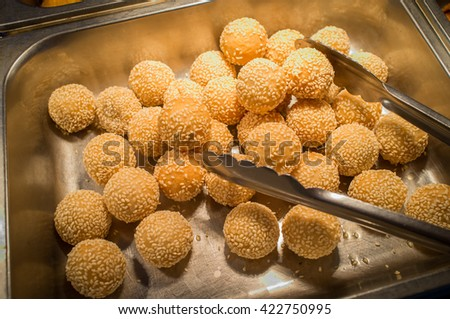Chinese dessert sesame donuts in self serve buffet tray - stock photo