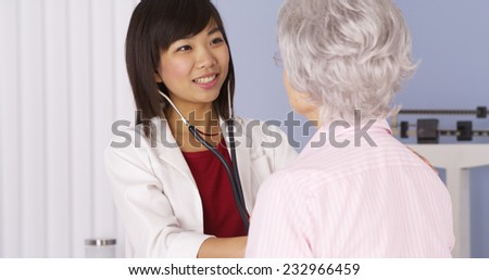 Chinese doctor listening to senior patient's heart - stock photo