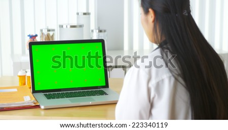 Chinese doctor talking to laptop with green screen - stock photo