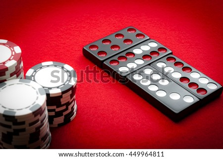 Chinese dominos and casino chips on a red felt table background in the vintage casino game of Pai Gow tiles