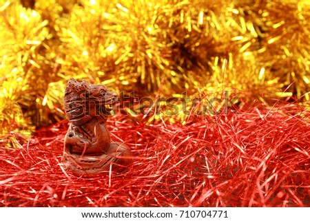 Chinese dragon figurine on a festive red and gold glitter background