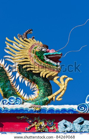Chinese dragon statue with blue sky background.