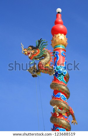 Chinese dragon with lamp decorated on the red post against blue sky - stock photo