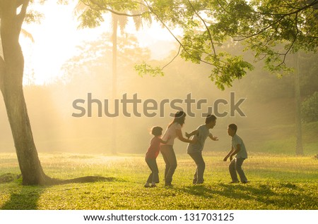 chinese family having quality time playing at outdoor park - stock photo