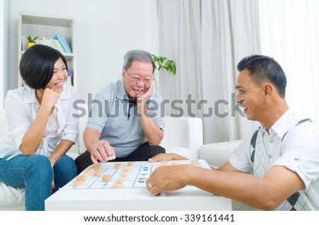 Chinese family playing Chinese chess at home, senior father with his  adult son and daughter.