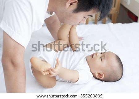 Chinese father and son playing in bed, real people