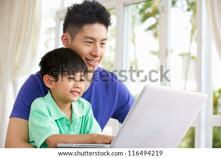 Chinese Father And Son Sitting At Desk Using Laptop At Home - stock photo
