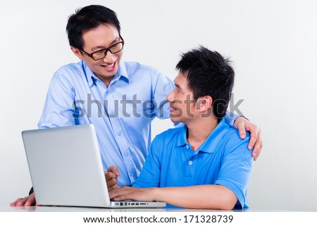 Chinese father helps his son with knowledge and experience for his complex and complicated homework assignments for the next day at school - stock photo