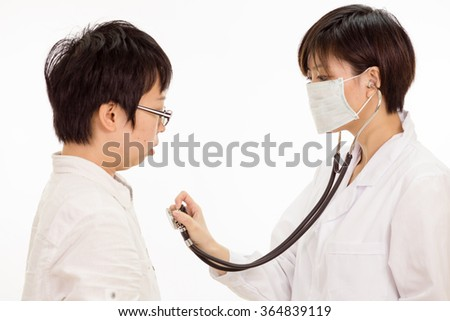Chinese female doctor checking patient's heart with stethoscope