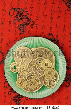 Chinese feng shui coins in a plate,the background is tapestry with traditional pattern. - stock photo