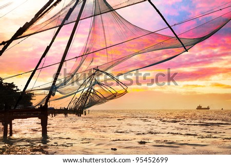 Chinese Fishing nets and small ship at dramatic sunset sky background in Kochi, Kerala, India - stock photo