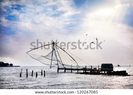 Chinese Fishing nets at blue cloudy sky background on Vypeen Island in Kochi, Kerala, India - stock photo