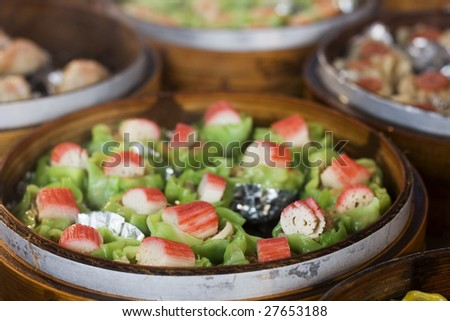 Chinese food being steam in 'steamer baskets'.  This is a form of 'dim sum'. - stock photo