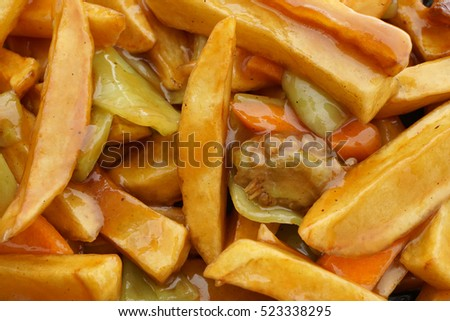 Chinese food. Fried potato chips in sauce. Closeup.