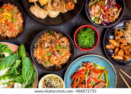 Chinese food on dark wooden table. Noodles, fried rice, dumplings, stir fry chicken, dim sum, spring rolls, bean sprouts, bok choy. Chinese cuisine set. Dinner party. Top view. Chinese restaurant