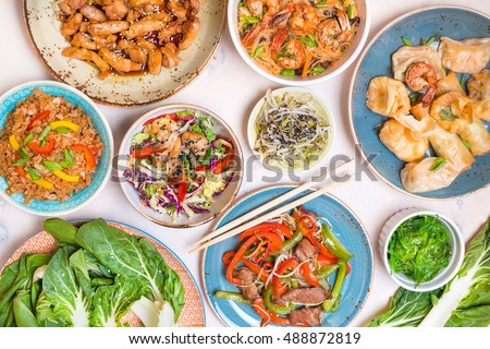 Chinese food on white wooden table. Noodles, fried rice, dumplings, stir fry chicken, dim sum, spring rolls, bean sprouts, bok choy. Chinese cuisine set. Dinner party. Top view. Chinese restaurant