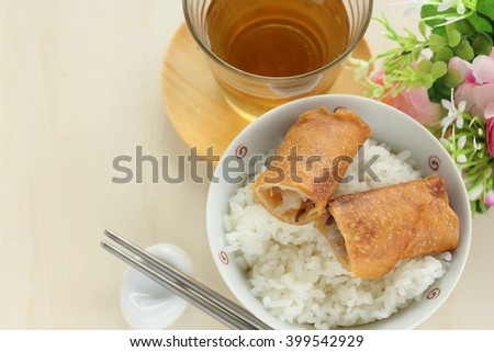 Chinese food, spring roll in half on rice with tea