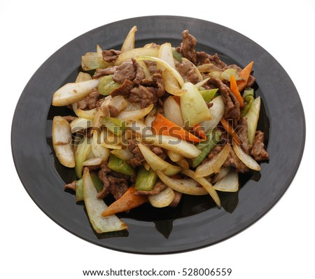 Chinese food. Veal with onions and vegetables in black plate isolated on white. Closeup.