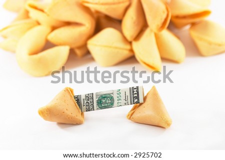 Chinese Fortune Cookie open with money, cash neatly folded inside the snack, on white background, many behind, to show one out of many. - stock photo