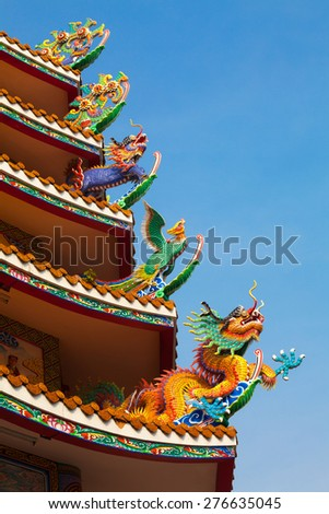 Chinese four symbols animals Dragon ,phoenix ,kilen sculpture on public Chinese temple roof with blue sky - stock photo