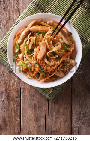 Chinese fried noodles with chicken and vegetables. vertical top view  - stock photo