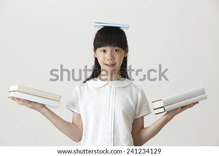 chinese girl balancing with books - stock photo