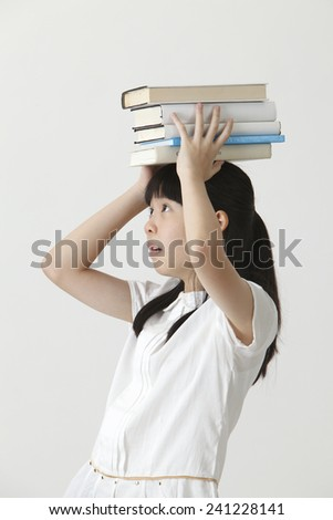 chinese girl holding stack of on her head