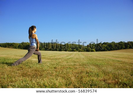 Chinese girl practicing yoga in a summer meadow. - stock photo