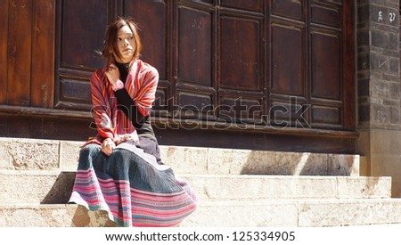 chinese girl sit on stairs and look back in sun ray in old town Lijiang in Yunnan province