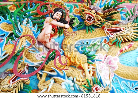 Chinese God Fighting with Dragon Sculpture Painting on wall.in Chinese Buddha Temple in Asia , Thailand - stock photo